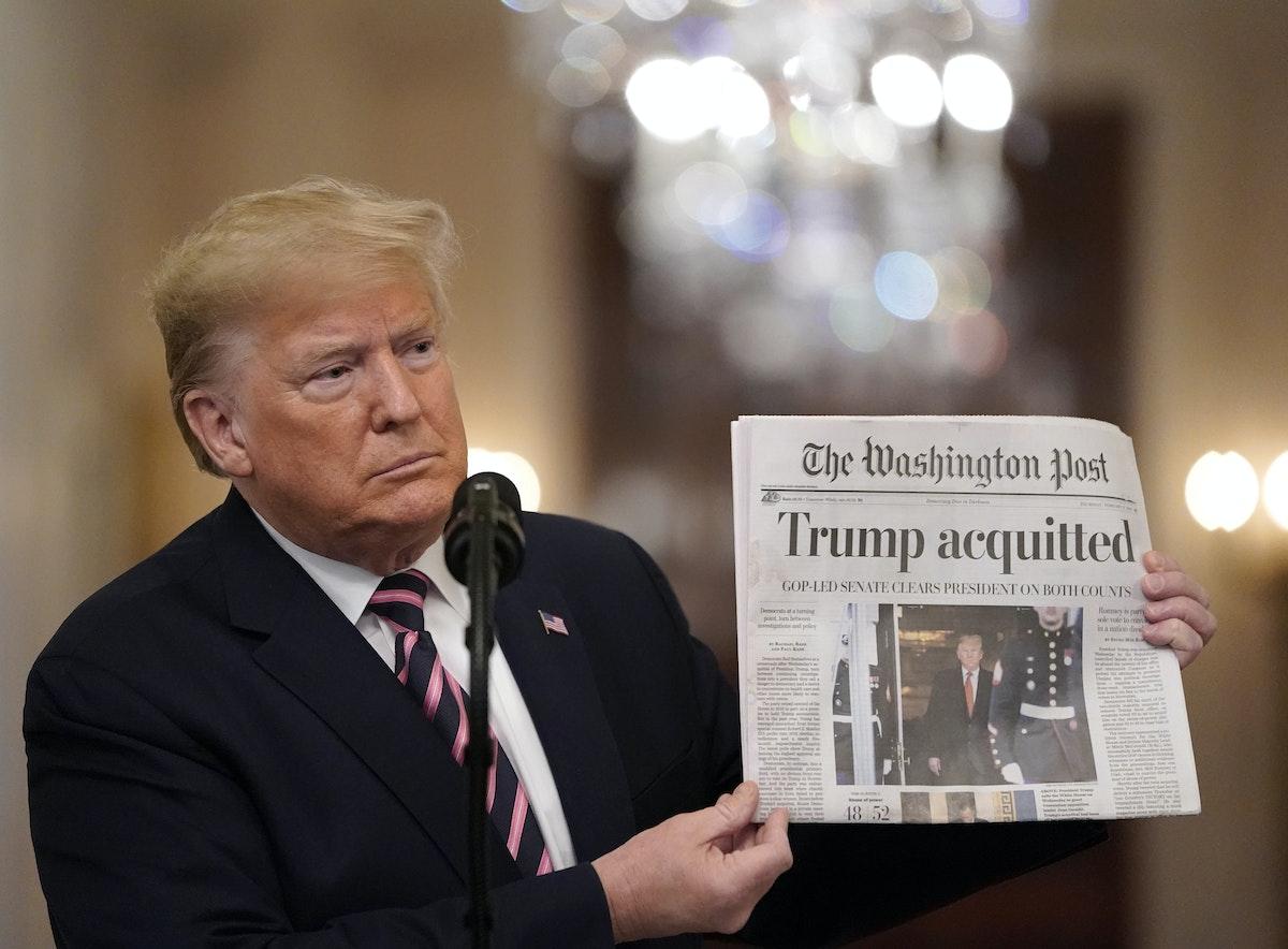 ترامب يرفع صحيفة يظهر على صفحتها الأولى خبر تبرئته خلال مؤتمر في البيت الأبيض - AFP