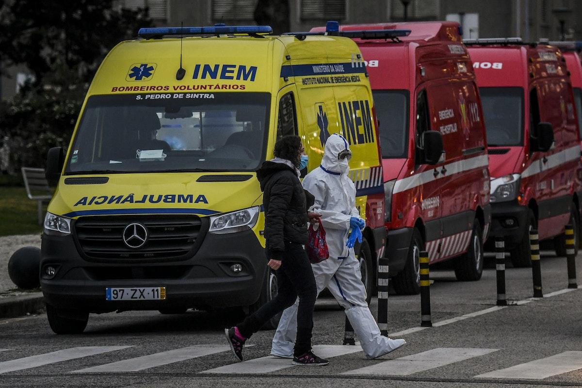 عامل صحي يسير بجوار عدد كبير من سيارات الإسعاف بالقرب من مستشفى في العاصمة البرتغالية لشبونة 28 يناير 2021 - AFP