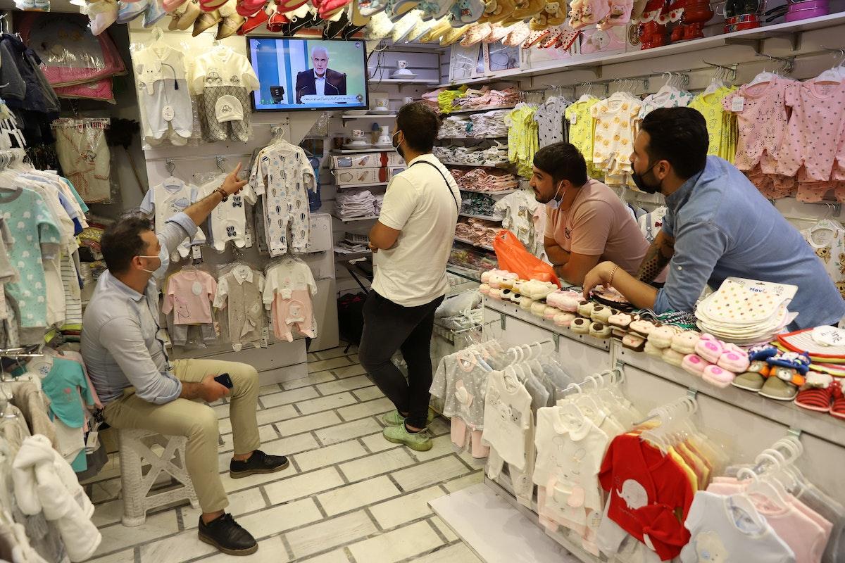 يتابعون المناظرة الانتخابية لمرشحي الرئاسة داخل متجر في طهران - 8 يونيو 2021 - REUTERS
