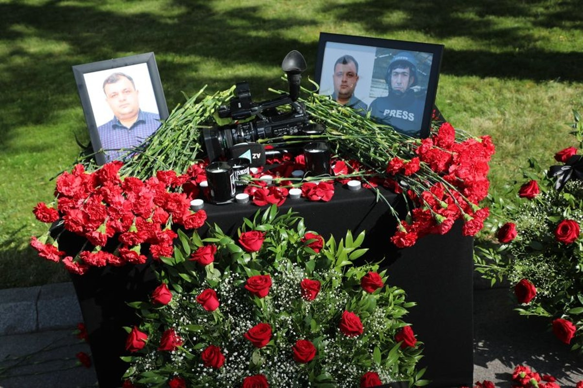 صور الصحافيين تتوسطها كاميرا خلال دفنهما في أذربيجان - facebook.com/aztvresmi