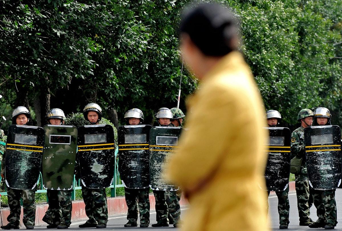 امرأة تمر أمام جنود صينيين خلال مظاهرات الأويغور التي شهدها إقليم شينجيانغ - 4 سبتمبر 2009 - AFP