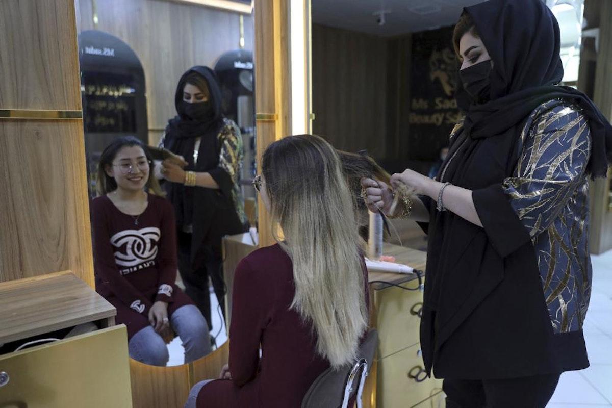 السيدة سادات، مالكة صالون تجميل في كابول، تصفّف شعر زبونة - 25 أبريل 2021 - AP