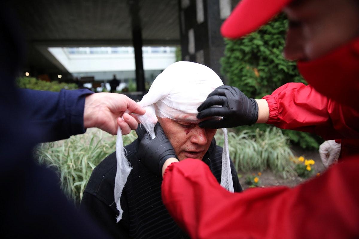 يساعدون محتجاً جُرح خلال تظاهرة في مينسك - 11 أكتوبر 2020     - via REUTERS