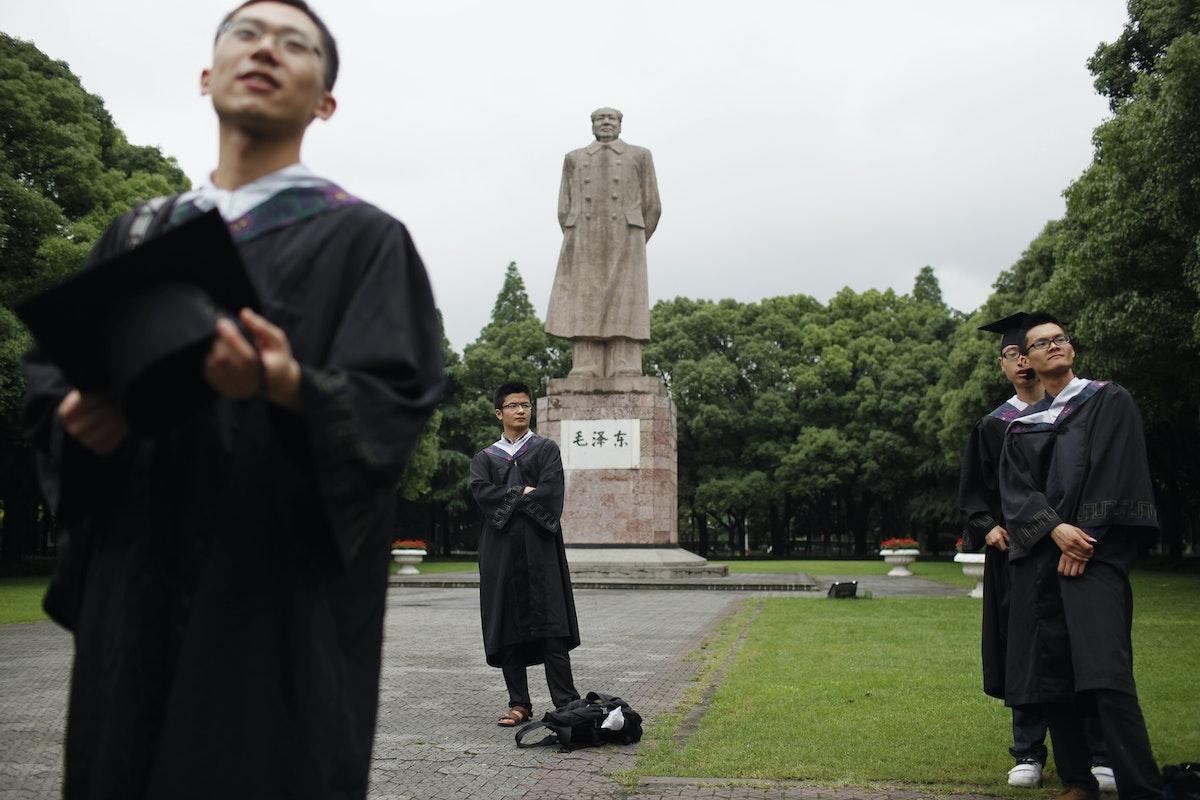 خرّيجون في جامعة فودان بشنغهاي يلتقطون صورة أمام تمثال للزعيم الصيني الراحل ماو تسي تونغ - 28 يونيو 2013 - REUTERS