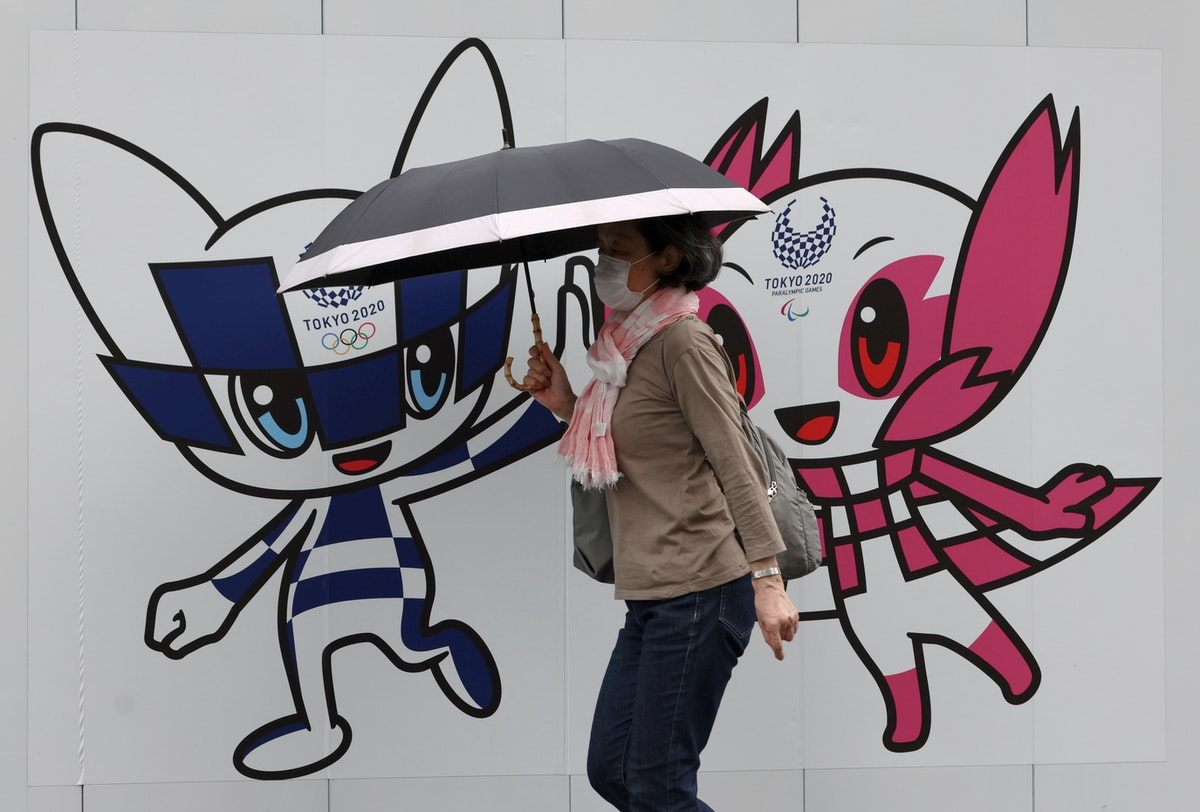 سيدة يابانية تمر من أمام تميمتي الألعاب الأولمبية والبارالمبية في طوكيو - REUTERS