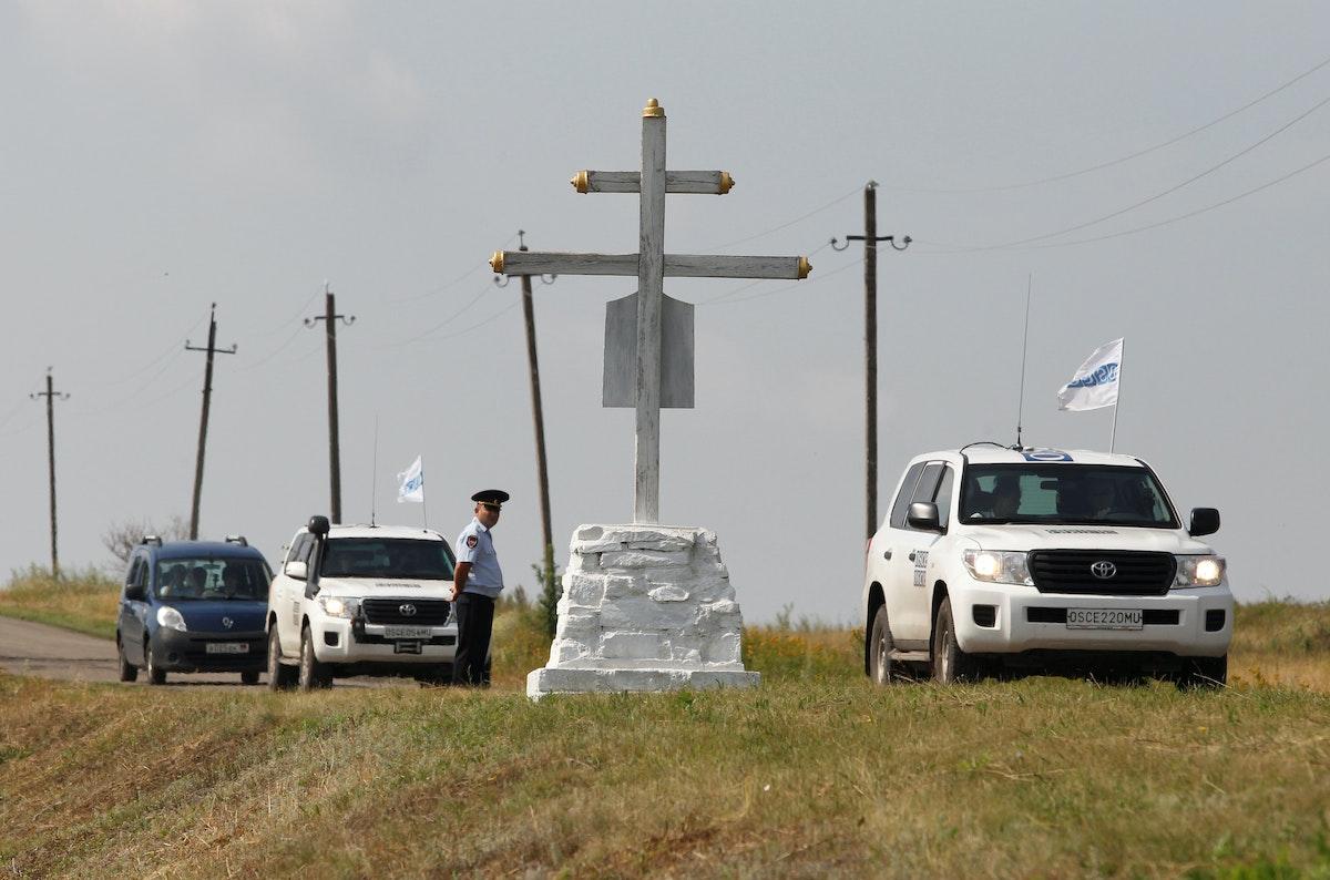 سيارات منظمة الأمن والتعاون في أوروبا تسير بالقرب من النصب التذكاري لموقع تحطم الطائرة الماليزية - REUTERS