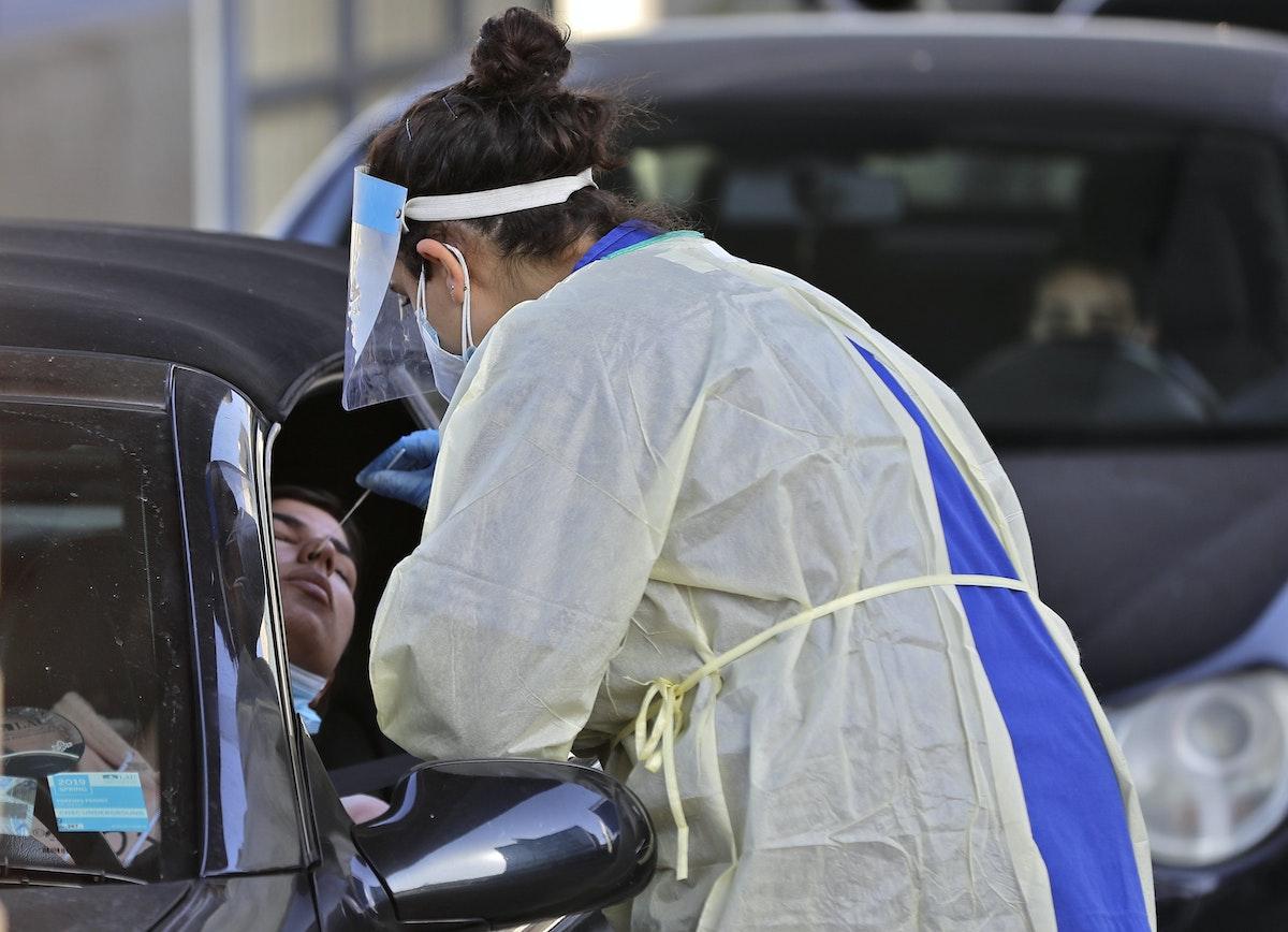 عاملة بالقطاع الطبي اللبناني تأخذ مسحة لأحد اللبنانيين من سيارته، قبل يومين من الإغلاق الكامل. 12 يناير 2021 - AFP