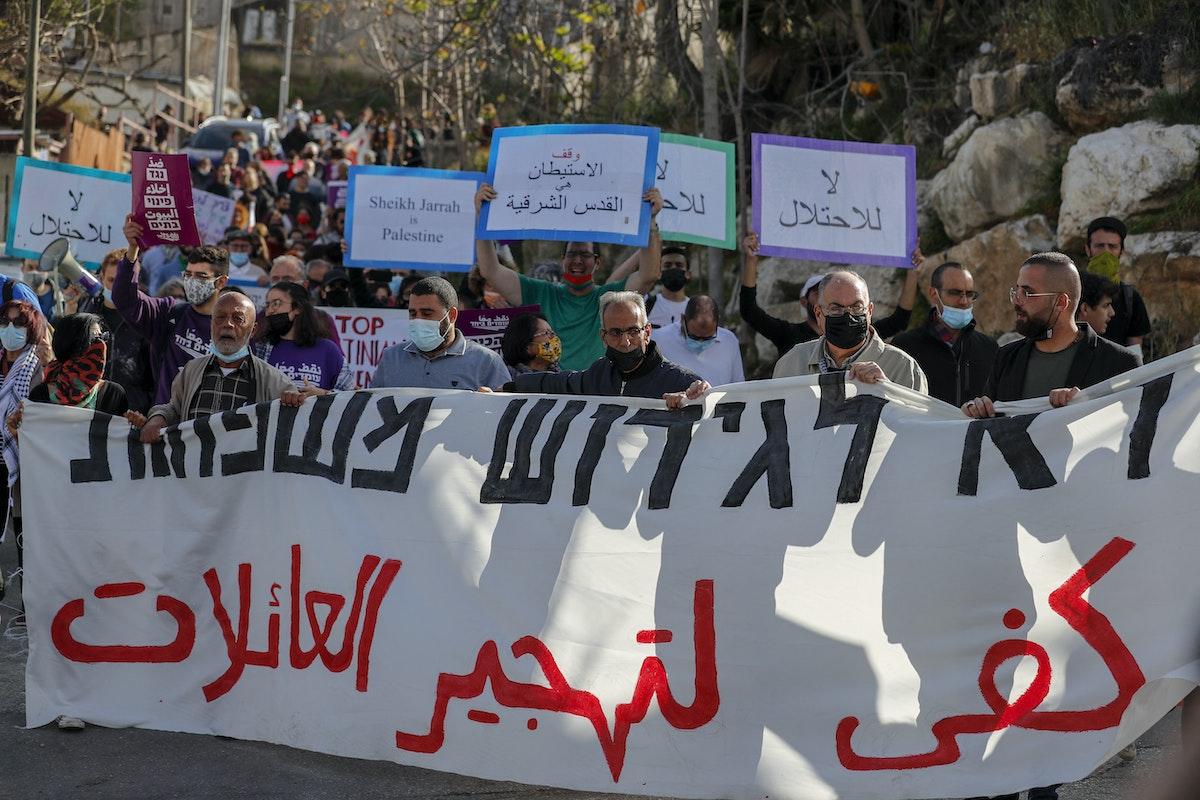 متظاهرون فلسطينيون يرفعون لافتات ضد عمليات الاستيطان الإسرائيلي في حي الشيخ جراح في القدس-9 أبريل 2021 - AFP