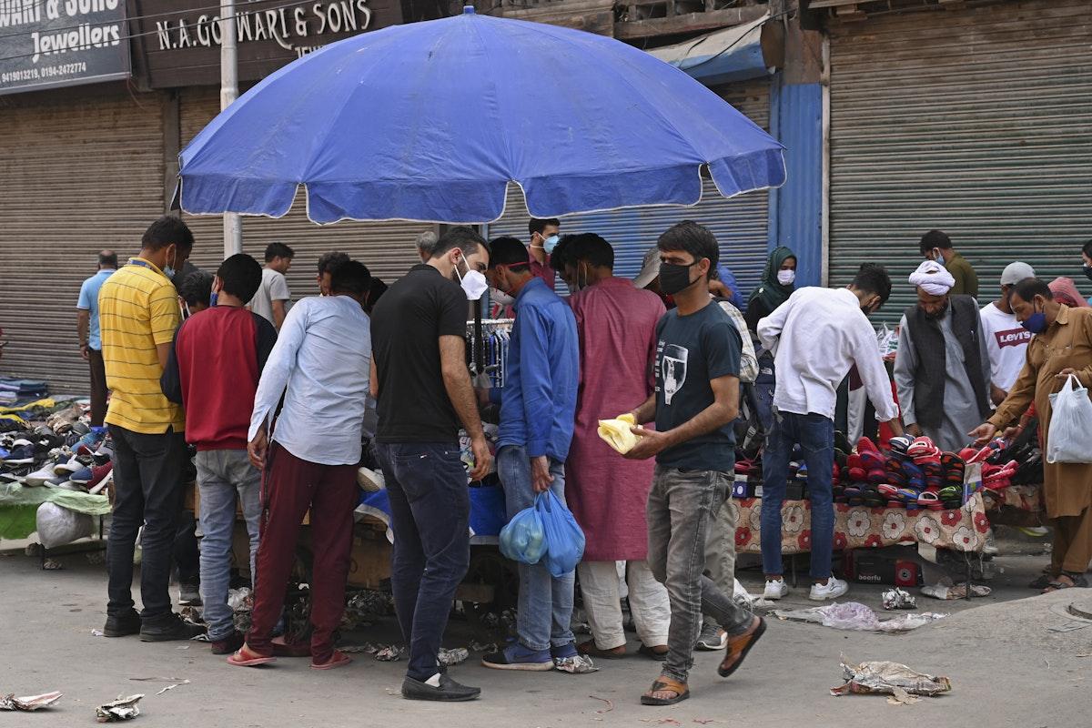أشخاص يتبضعون في إحدى الأسواق بعد التخفيف الجزئي لقيود الإغلاق المفروضة للحد من انتشار كورونا في سريناغار، الهند. 7 يونيو 2021 - AFP