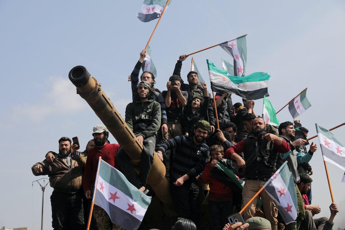 يعتلون آلية عسكرية تركية في مدينة إدلب السورية، احتجاجاً على اتفاق لتسيير دوريات روسية - تركية مشتركة - 15 مارس 2020 - REUTERS