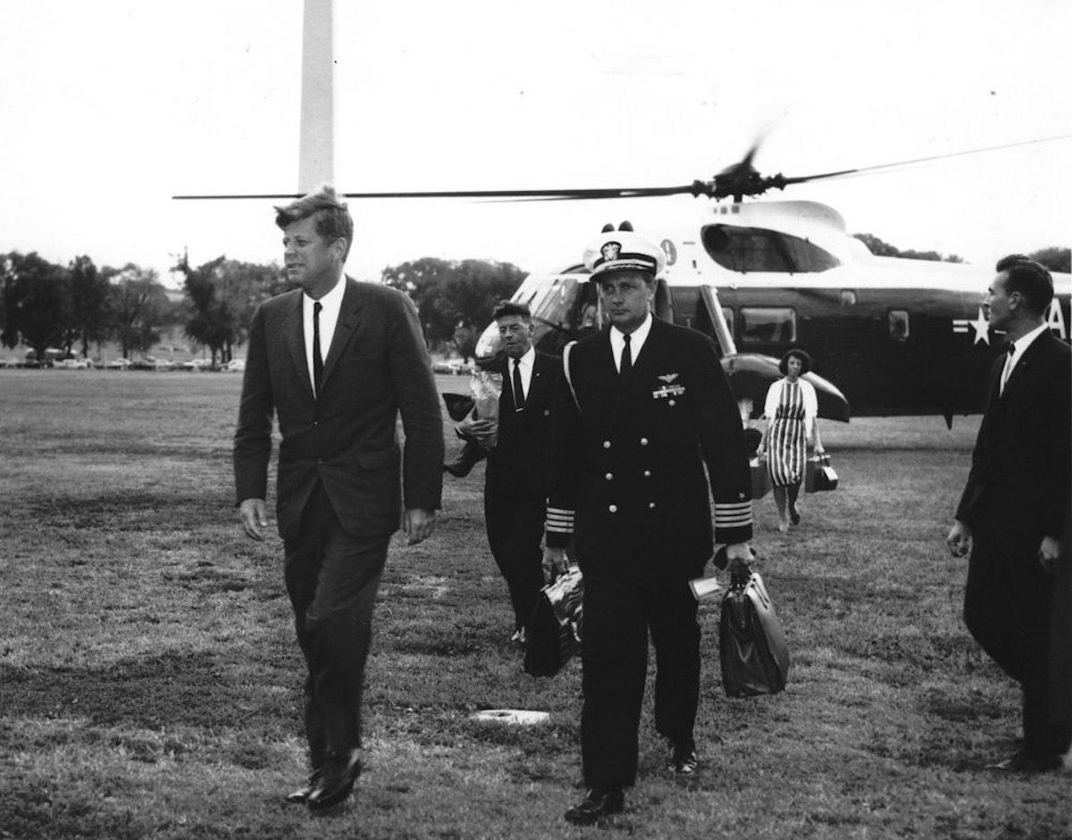 الرئيس الأميركي الأسبق جون كينيدي عائداً إلى البيت الأبيض ويرافقه ضابط يحمل حقيبة الرموز النووية- 1962