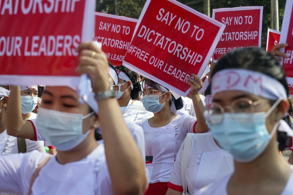 """ممرضات يرفعن لافتات منددة بـ""""الدكتاتورية"""" أثناء مسيرة ضد الانقلاب العسكري في يانغون، 13 فبراير 2021 - AFP"""