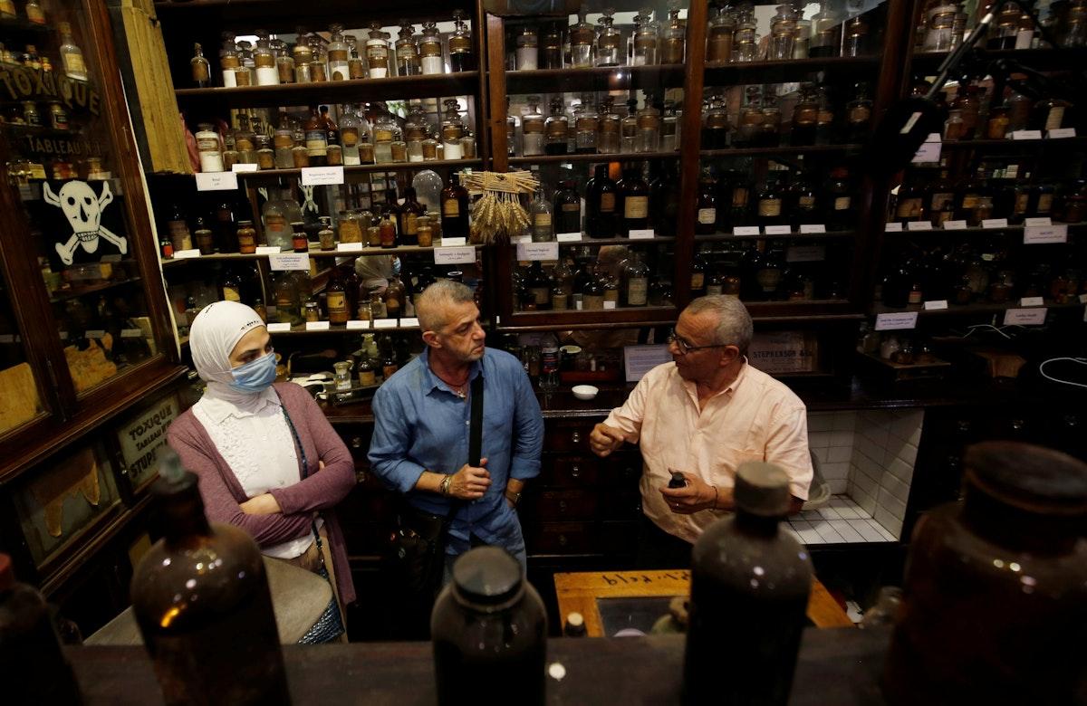 """زوار في صيدلية """"ستيفنسون"""" ، التي أسسها الصيدلاني الإنجليزي جورج ستيفنسون عام 1915، مع مديرها زهير إحسان (يمين) - REUTERS"""