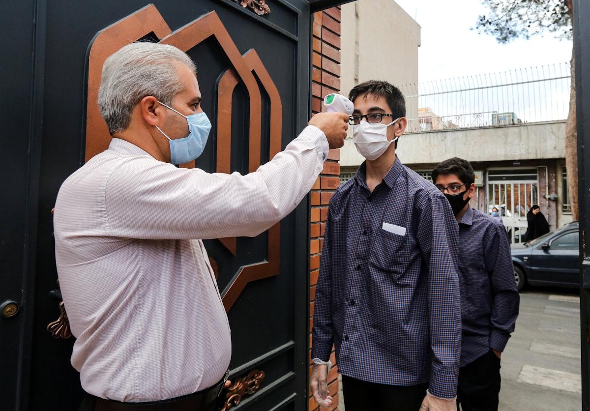 طلاب مدرسة يقيسون درجات الحرارة خلال دخولهم إلى مدرستهم في طهران 5 سبتمبر 2020 - AFP