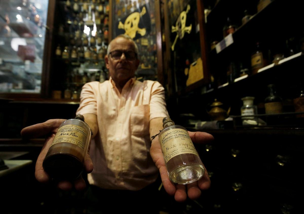 """زهير إحسان، يحمل زجاجات الأدوية القديمة في صيدلية """"ستيفنسون""""، التي أسسها الصيدلاني الإنجليزي جورج ستيفنسون عام 1915 - REUTERS"""