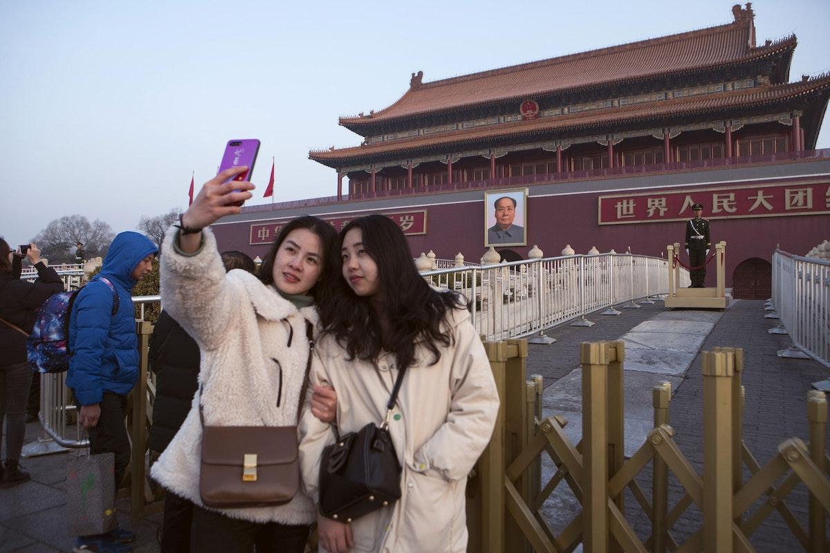 """فتاتان تلتقطان صورة """"سيلفي"""" أمام صورة للزعيم الصيني الراحل ماو تسي تونغ في ساحة تيانانمن ببكين - 4 مارس 2019 - Bloomberg"""