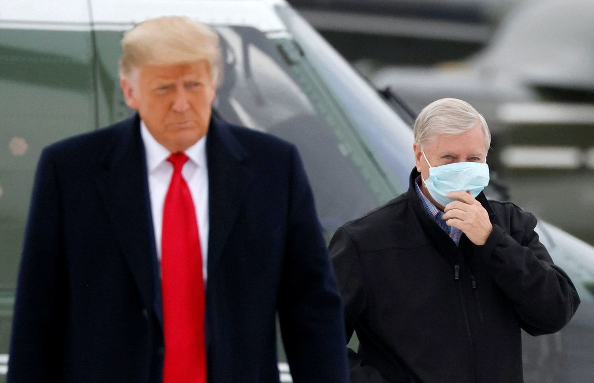 السيناتور ليندسي غراهام يرافق الرئيس الأميركي بعد عودته من زيارة الجدار الحدودي في تكساس - REUTERS