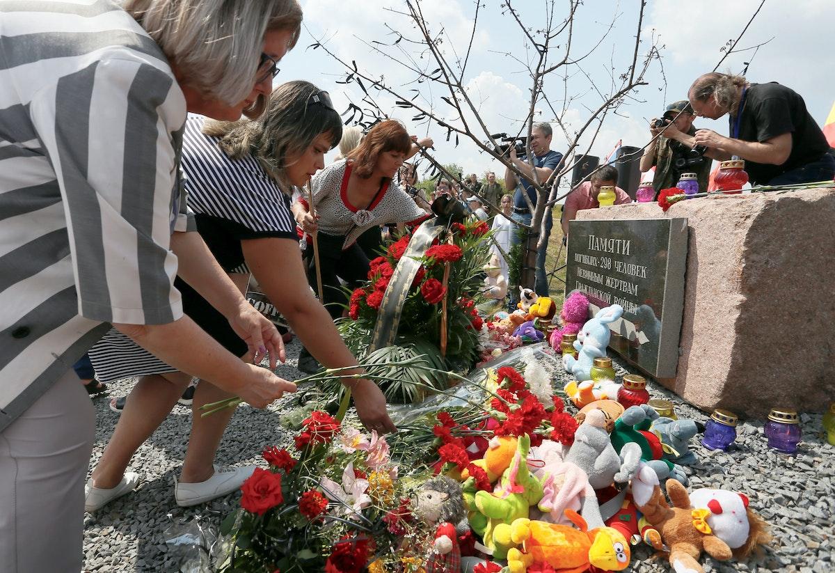 أشخاص يضعون الورود على النصب التذكاري في موقع تحطم الطائرة الماليزية في أوكرانيا - REUTERS