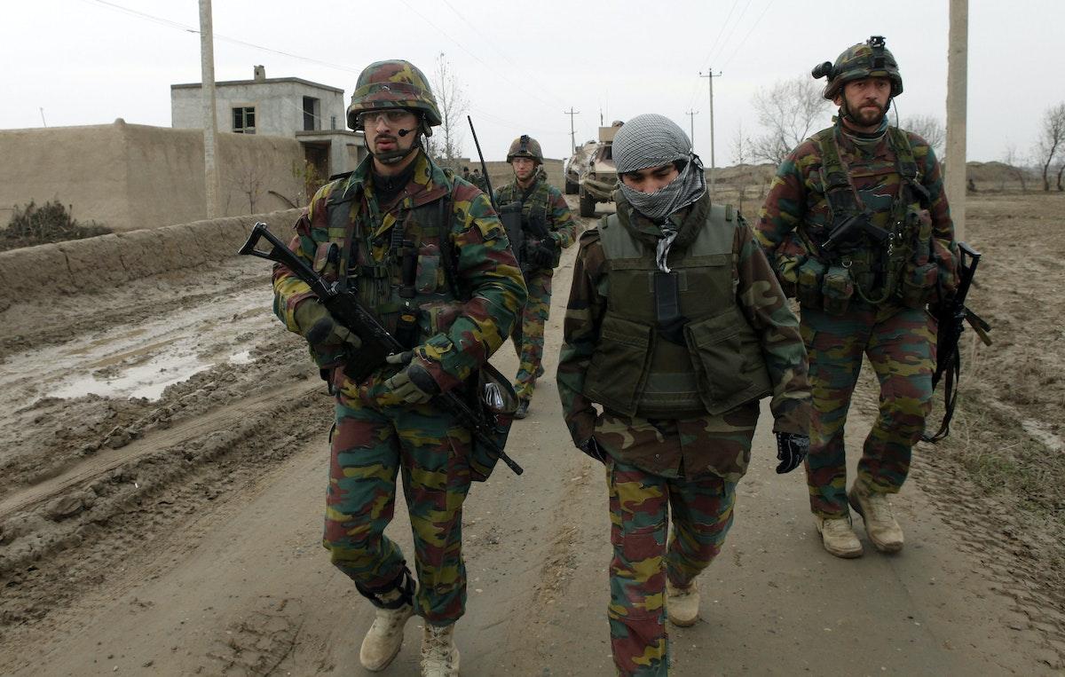 مترجم أفغاني يتوسّط جنديَين بلجيكيين خلال عملية لمسح ألغام في ضواحي قندوز - 16 ديسمبر 2009 - REUTERS
