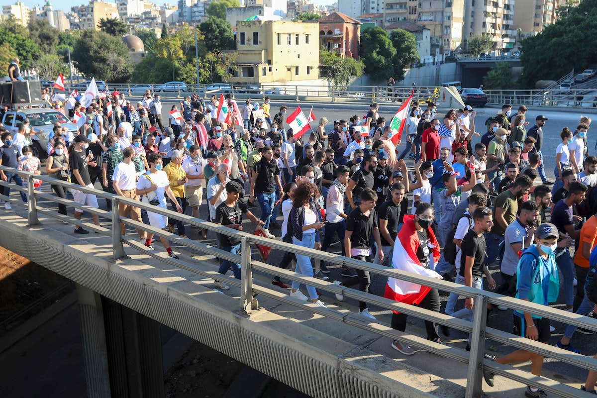 Lebanese demonstrators wave the national flag during a demonstration, marking the first anniversary of a non-sectarian protest movement, in the capital Beirut on October 17, 2020. - A whirlwind of hope and despair has gripped the country in the year since protests began, with an economic crisis and a devastating August 4 port explosion pushing Lebanon deeper into decay. Two governments have resigned since the movement started but the country's barons, many of them warlords from the 1975-90 civil war, remain firmly in power despite international as well as domestic pressure for change. (Photo by Anwar AMRO / AFP) - AFP