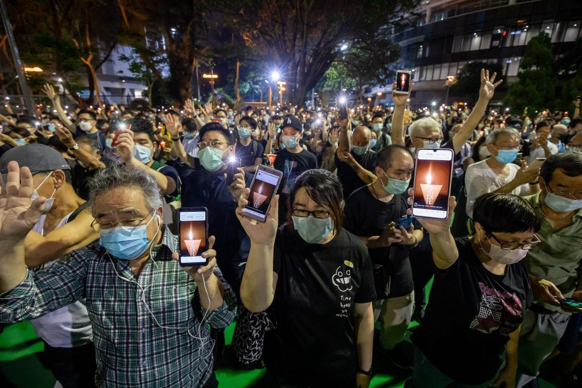 """يستخدمون هواتفهم الذكية في """"إضاءة شموع""""، في حديقة فيكتوريا بهونغ كونغ، إحياءً لذكرى أحداث تيانانمين - 4 يونيو 2020 - Bloomberg"""
