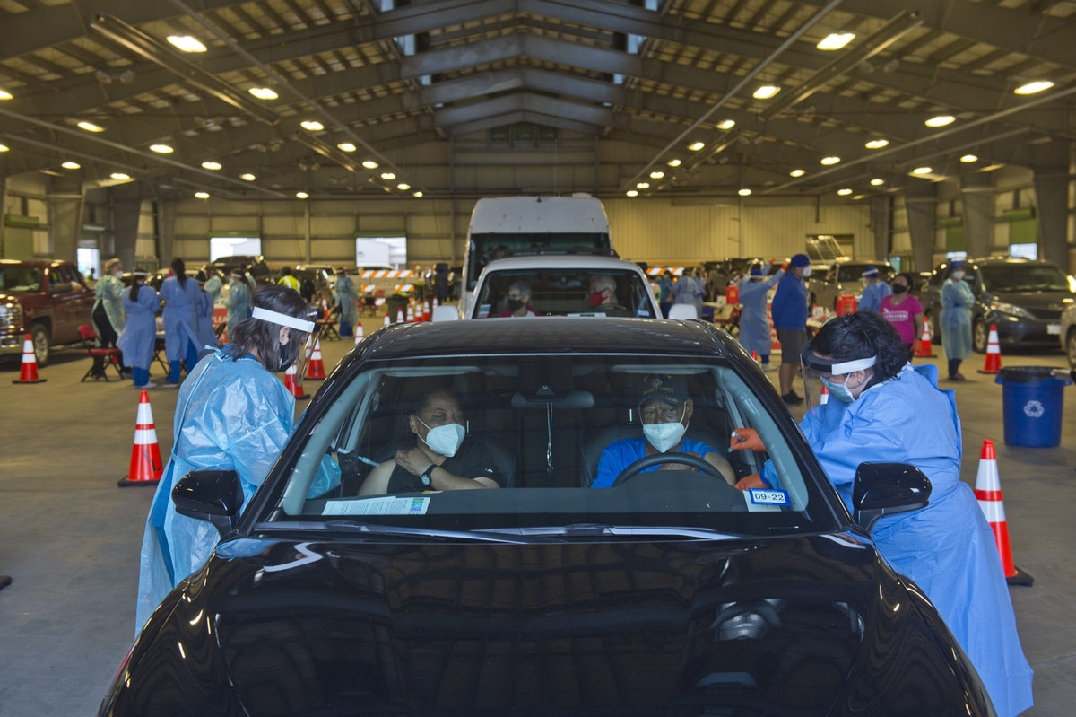 شخصان يتلقيان اللقاح داخل سيارة بمركز معارض في تكساس - 26 يناير 2021 - Bloomberg