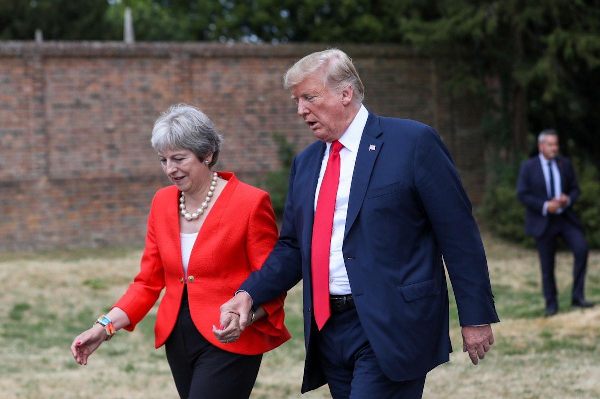 الرئيس الأميركي دونالد ترمب ممسكاً بيد رئيسة الوزراء البريطانية تيريزا ماي خلال لقائهما في المملكة المتحدة - 13 يوليو 2018 - Bloomberg