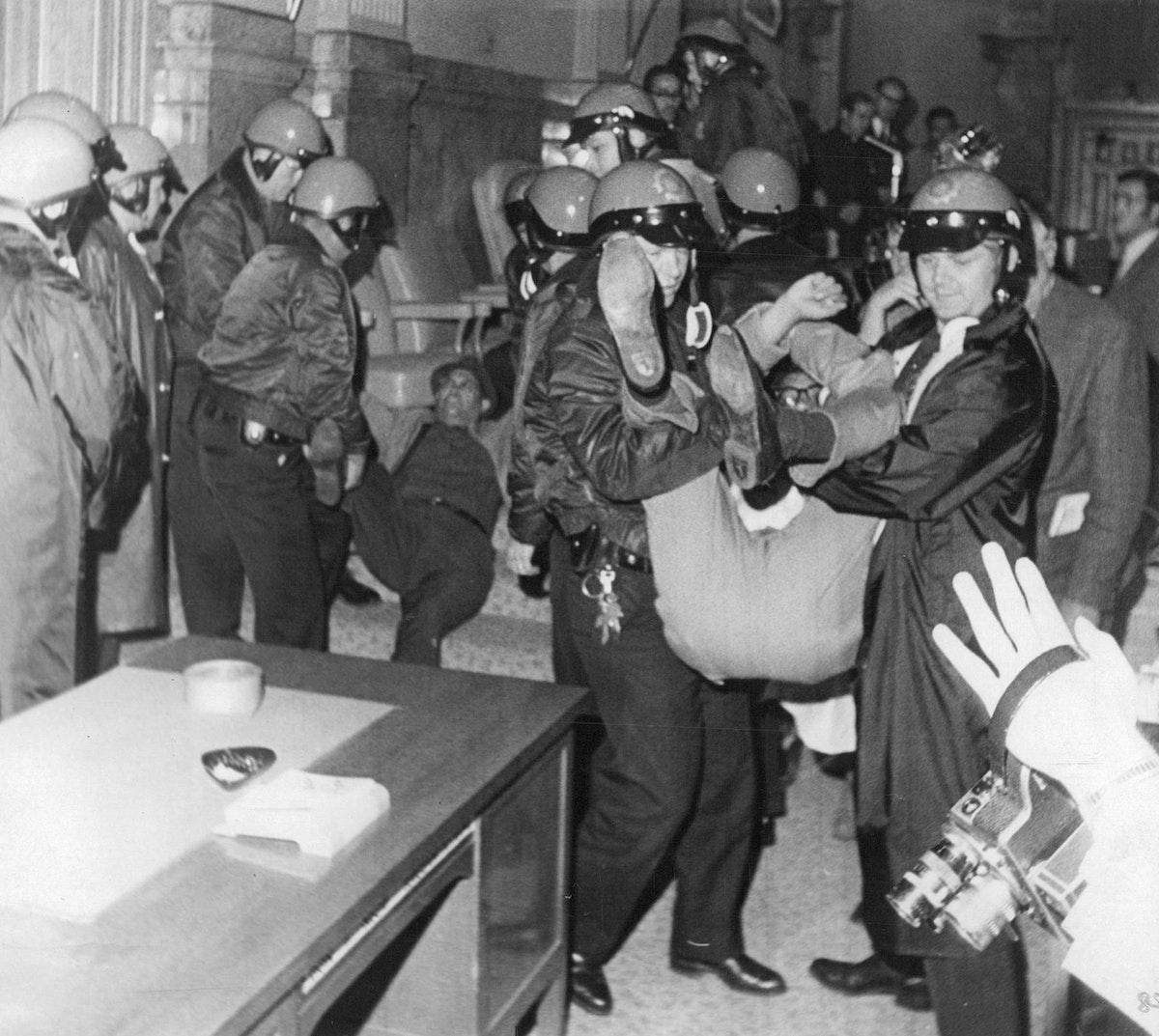 الشرطة الأميركية تخرج أحد المتظاهرين الغاضبين لدى اقتحامه مبنى الكابيتول في 6 مايو 1969 - Getty Images