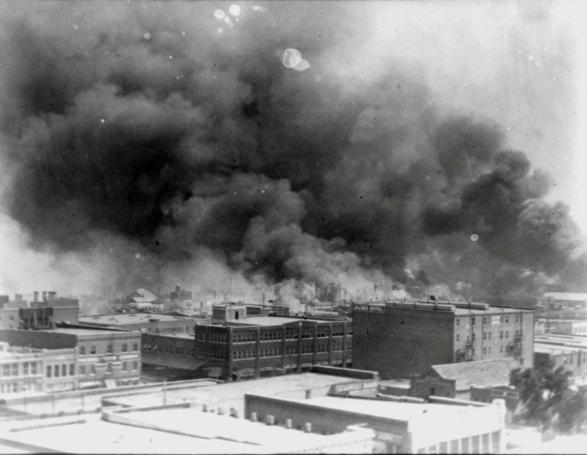 الدخان يتصاعد من المباني خلال مذبحة عام 1921 في تولسا - REUTERS