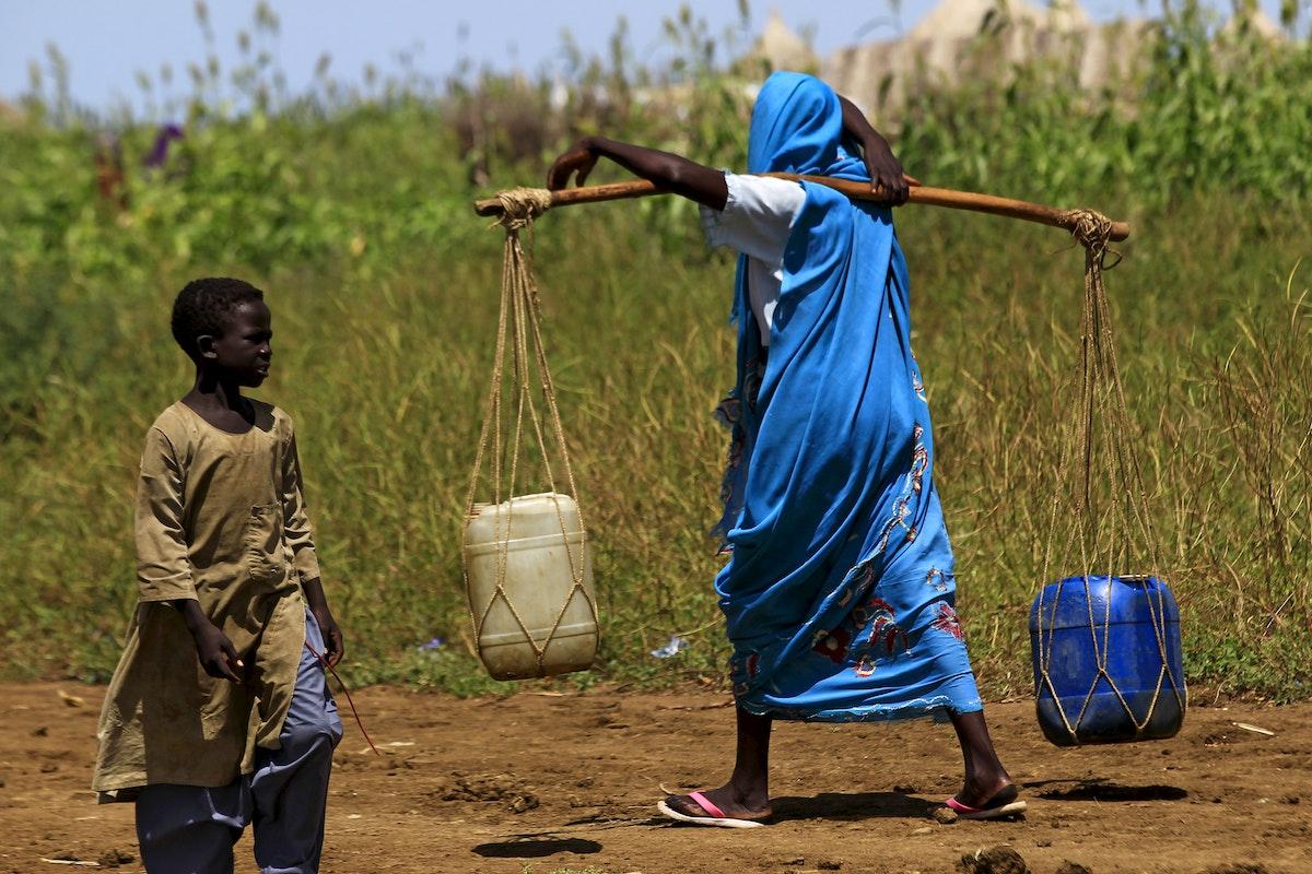 امرأة تحمل الماء في شرق الدمازين عاصمة ولاية النيل الأزرق بالسودان - REUTERS