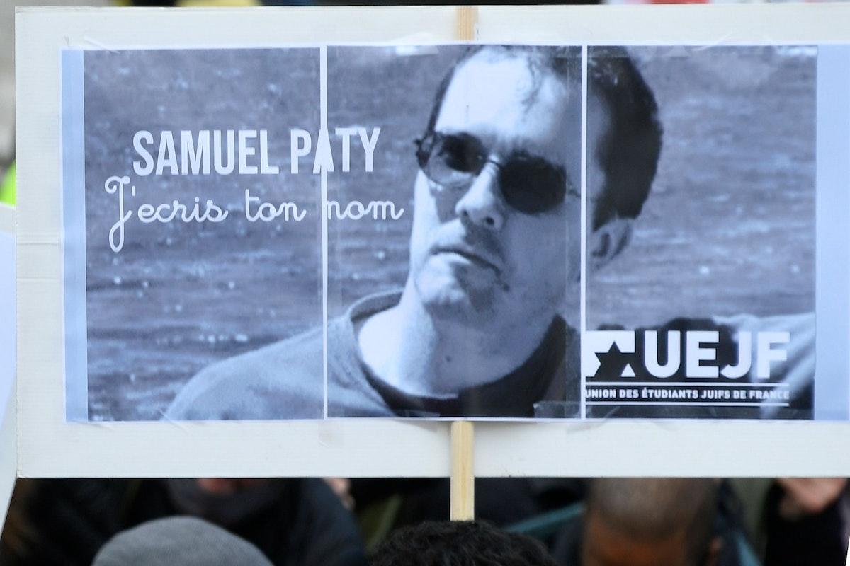 متظاهر يرفع صورة الأستاذ صامويل باتي، الذي راح ضحية عمل إرهابي الجمعة - AFP