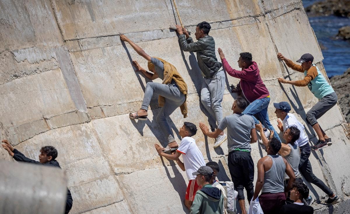 شباب يتسلّقون جداراً بعد محاولتهم عبور الحدود من المغرب إلى سبتة - 19 مايو 2021 - AFP