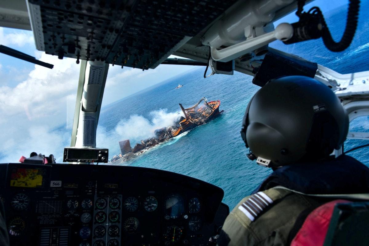 """طائرة تراقب الحريق المتصاعد من السفينة """"إم في إكس برس بيرل"""" أثناء غرقها قبالة ميناء كولومبو - REUTERS"""