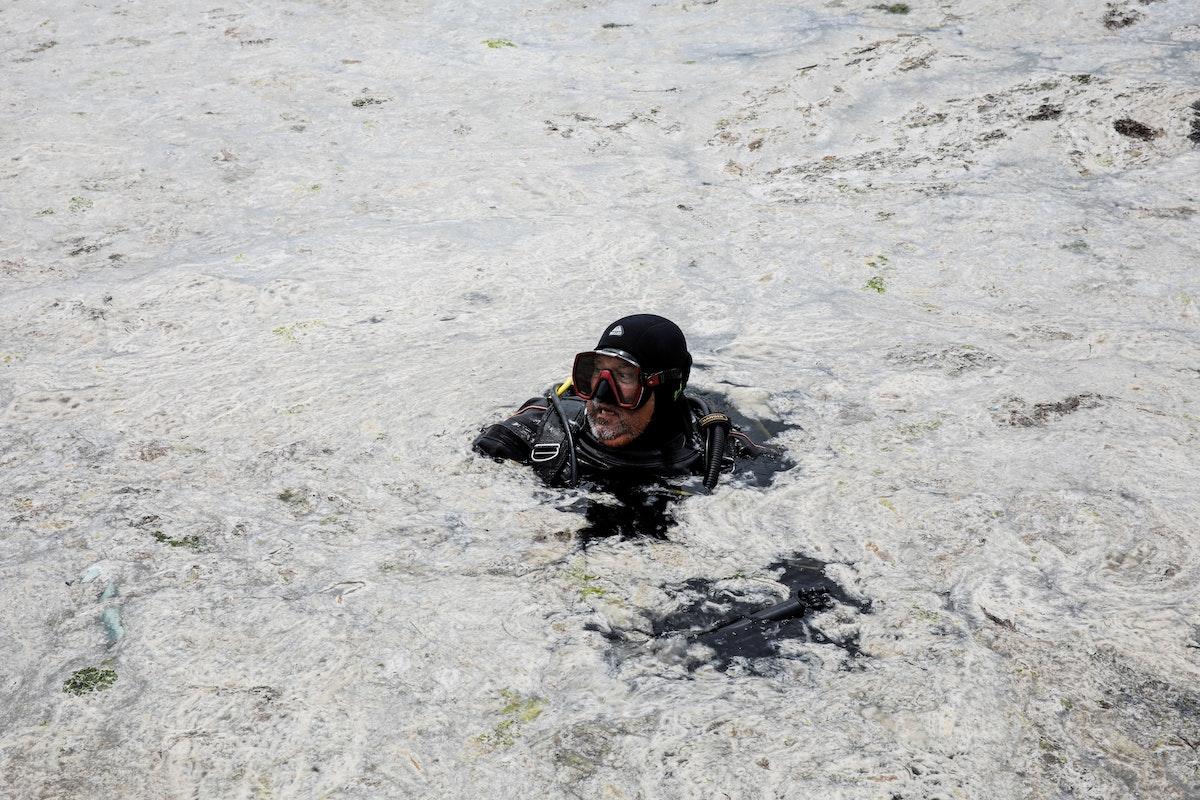 """الغواص والمخرج السينمائي تحسين جيلان يتفقد البحر المغطى بـ""""مخاط البحر"""" في شواطئ اسطنبول، تركيا، 8 يونيو 2021 - REUTERS"""