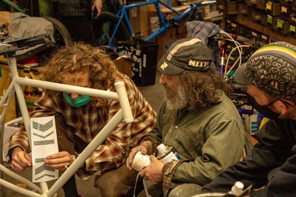 ستيفن بيلنكي (وسط) وموظفان يعملون على دراجة جونسون الجديدة قبل طلائها - www.inquirer.com