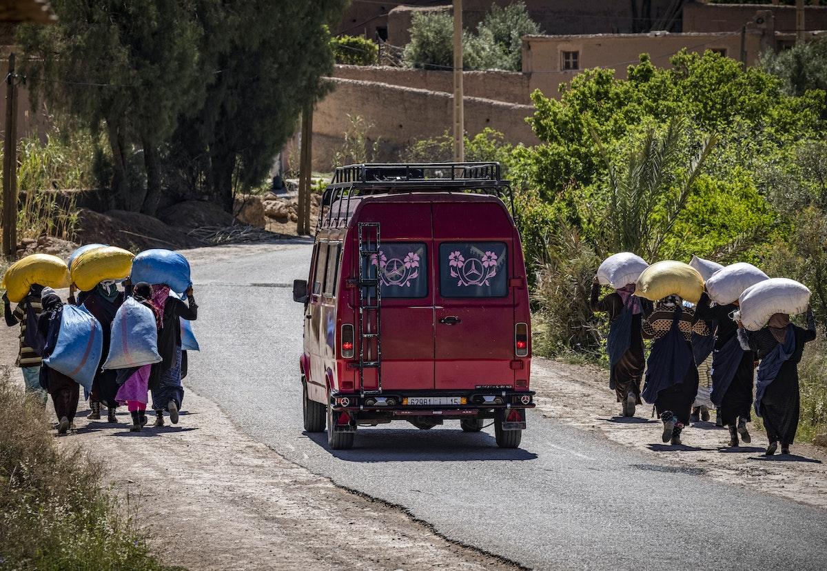 جانيات الورد يحملن أكياساً معبأة بما جنته أيديهن على مدى 6 ساعات من حقل بمدينة قلعة مكونة، 26 أبريل 2021 - AFP
