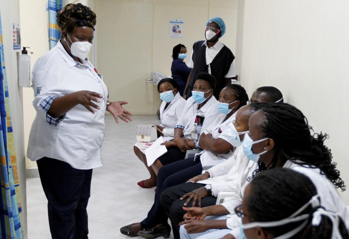 عاملة صحية تتحدث إلى زملائها وهم يستعدون لتلقي لقاح أسترازينيكا ضد فيروس كورونا بمستشفى في نيروبي ـ كينيا، 5 مارس 2021 - REUTERS