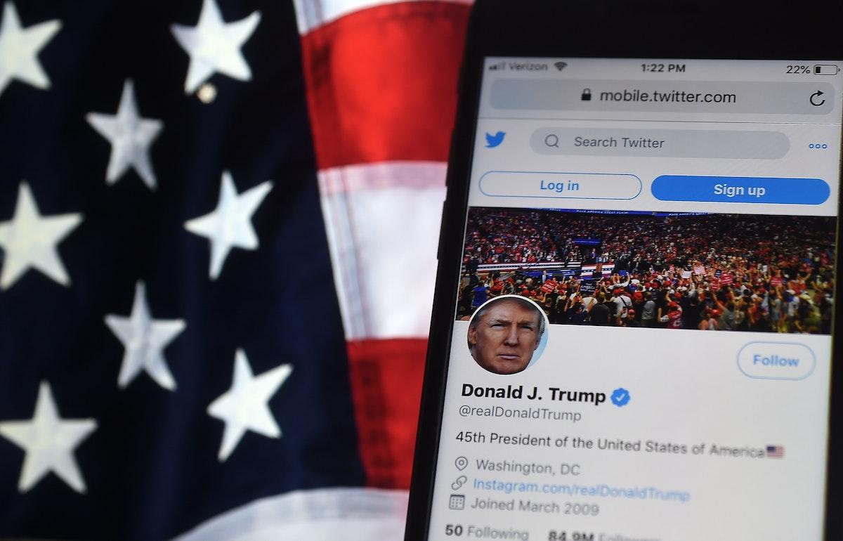 حساب الرئيس الأميركي دونالد ترمب في تويتر على هاتف محمول بجانب العلم الأميركي. - AFP