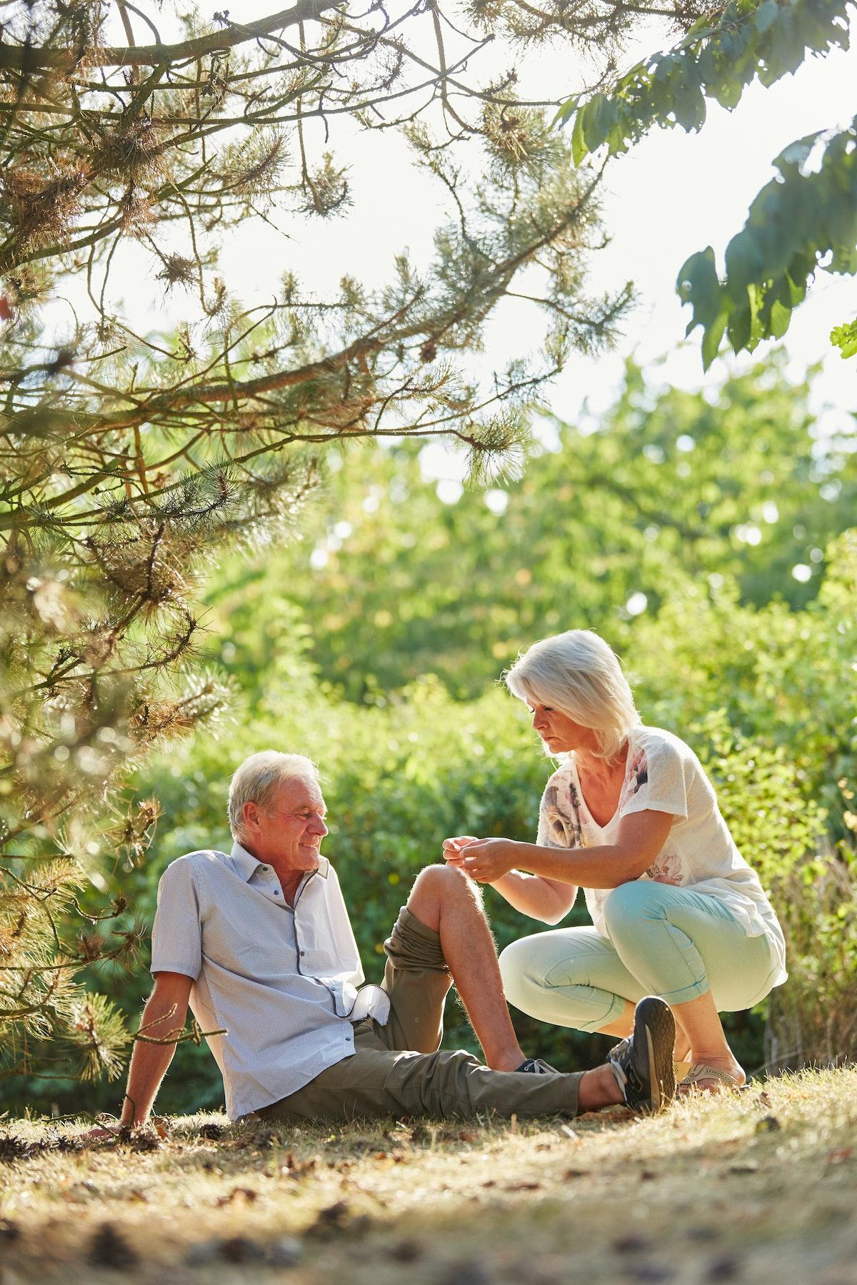 امرأة تساعد رجلاً على وضع ضمادة على ركبته - Getty Images