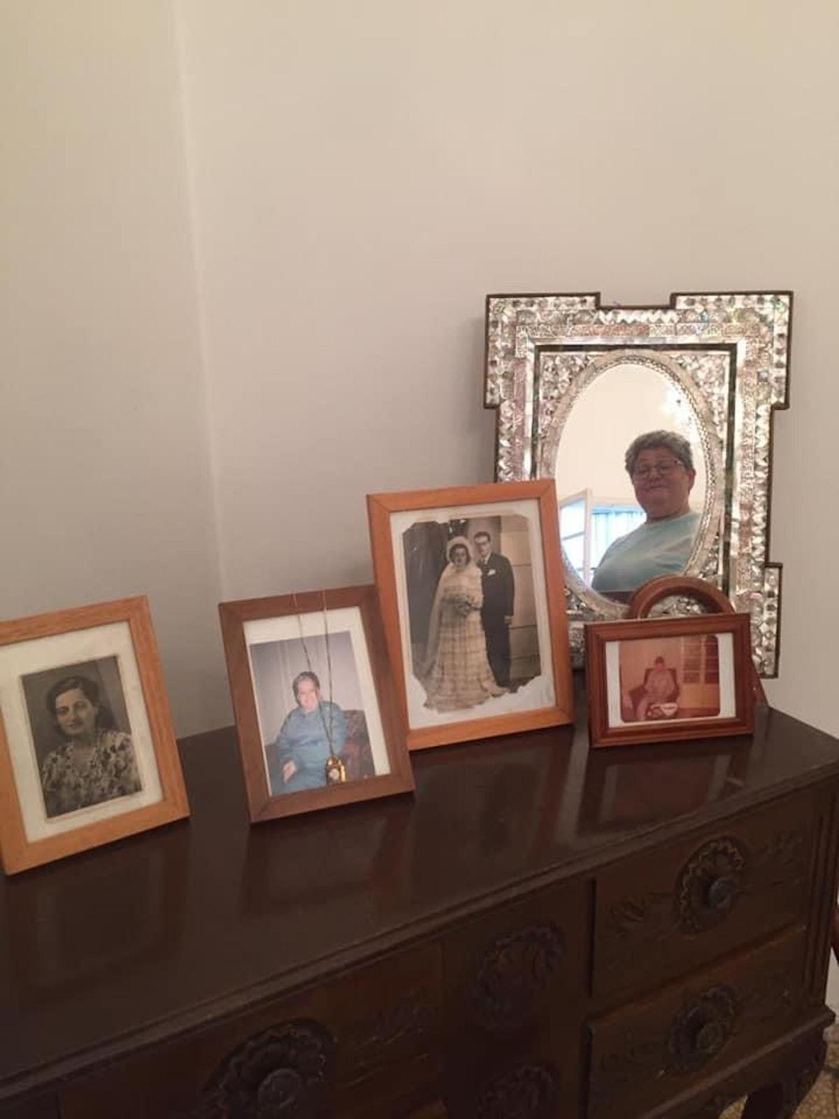 """انعكاس وجه رانية التنور في المرآة، إلى جانب صور فوتوغرافية قديمة، خلال عرض مسرحية """"وحدة"""" - الشرق"""