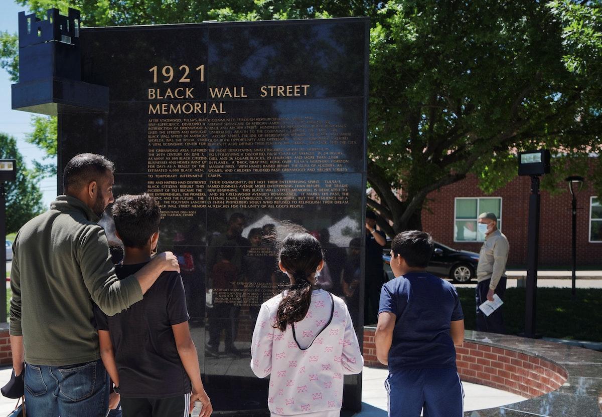 """عائلة تقرأ نصب""""بلاك وول ستريت"""" التذكاري خلال الاحتفالات بالذكرى المئوية لـ""""مذبحة تولسا"""". - REUTERS"""