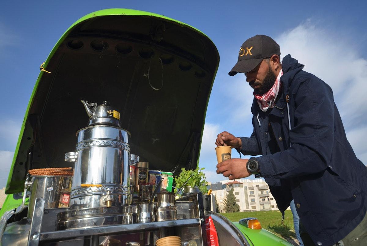 الشاب الأردني فادي يعدّ كوب القهوة في سيارته بأحد شوارع عمّان - REUTERS