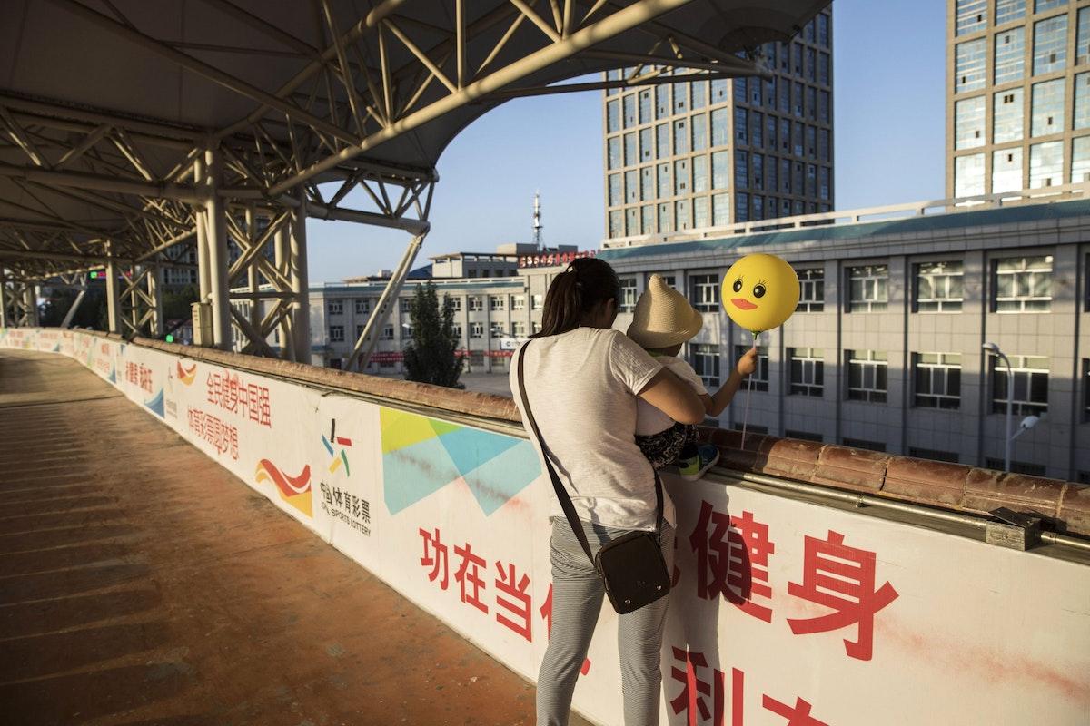 تحمل طفلاً في ملعب رياضي بمقاطعة تشينغهاي الصينية - 22 يوليو 2018 - Bloomberg