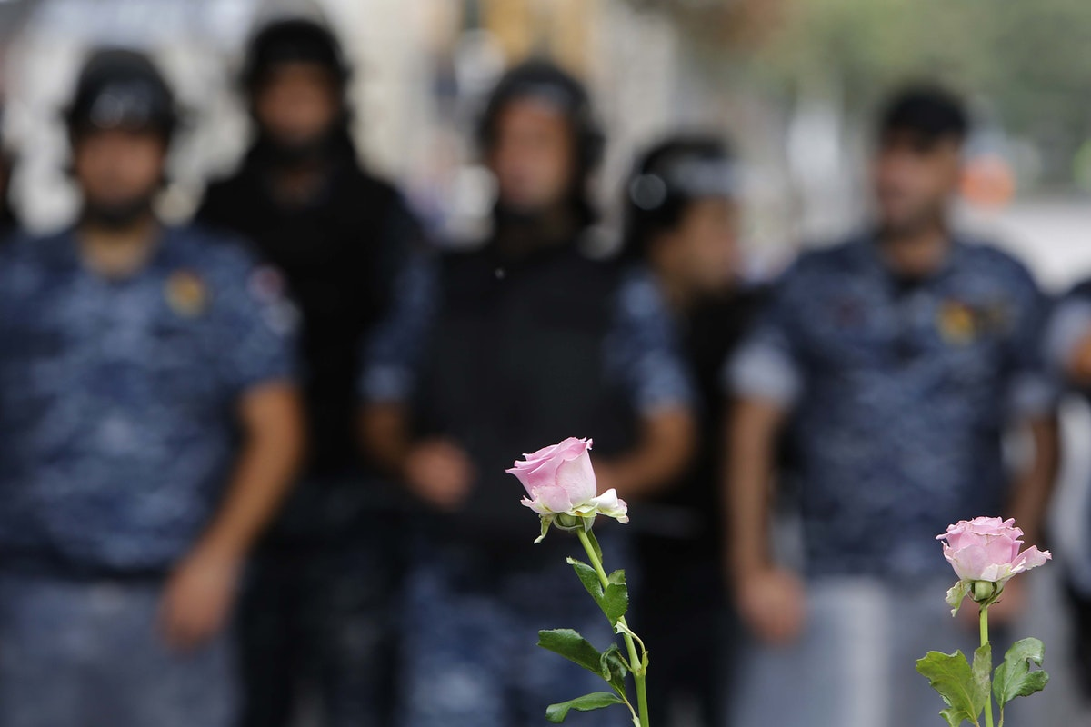 """صورة """"الوردة التي تواجه رجال الأمن"""" للمصور اللبناني مروان طحطح - الشرق"""