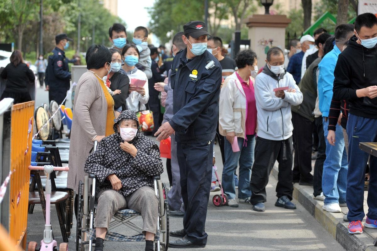 عشرات الأشخاص ينتظرون إجراء فحوص كورونا في مدينة تشينغداو شرقي الصين، 13 أكتوبر 2020 - AFP