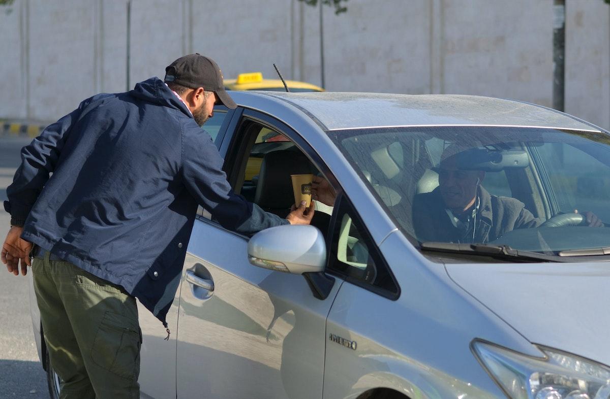 فادي أحمد يقدم المشروبات الساخنة لأصحاب السيارات وسائقي التاكسي في العاصمة الأردنية عمّان - REUTERS