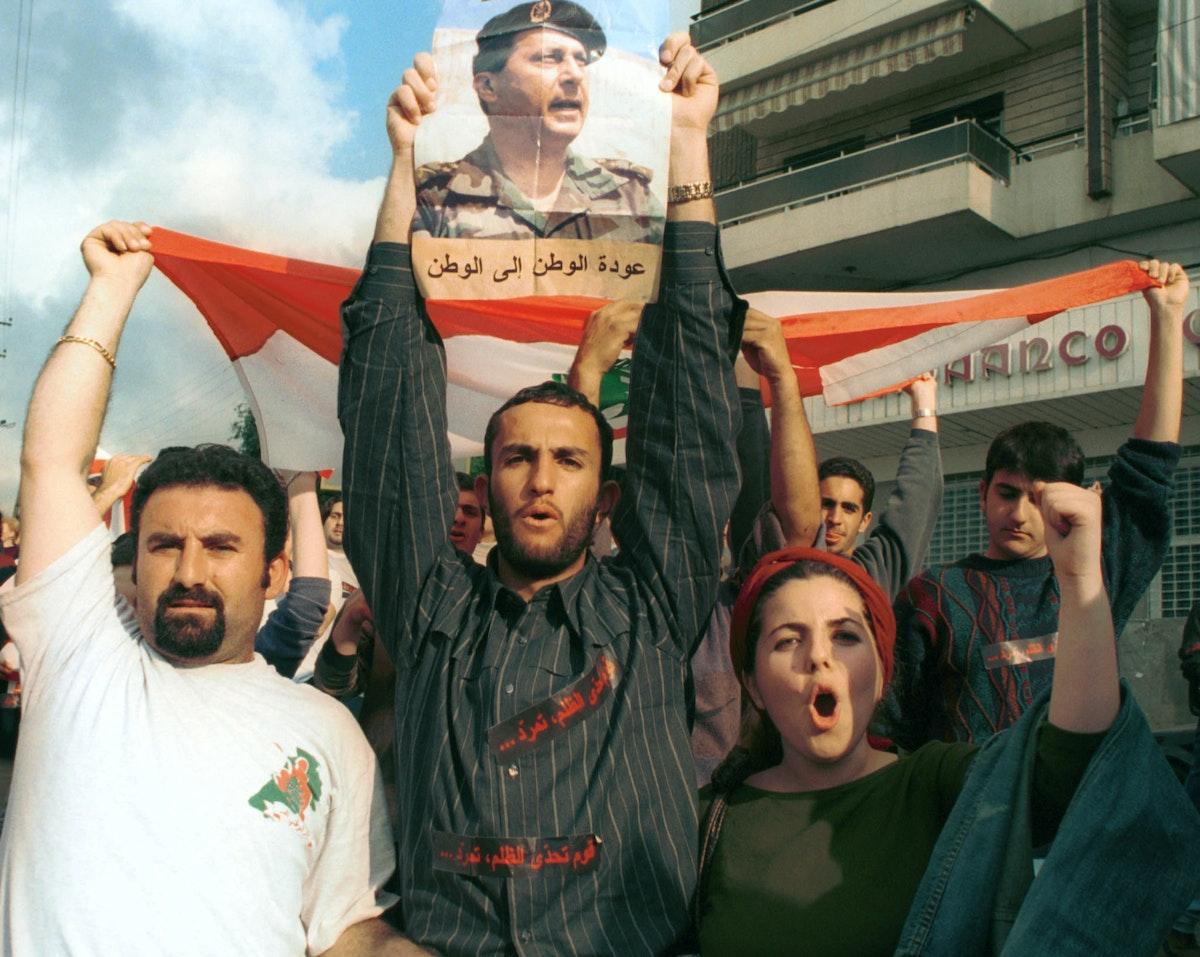 طلاب لبنانيون يرفعون صورة الجنرال ميشال عون المنفي في فرنسا خلال احتجاج في جامعة بيروت- 14 مارس 2001 - REUTERS