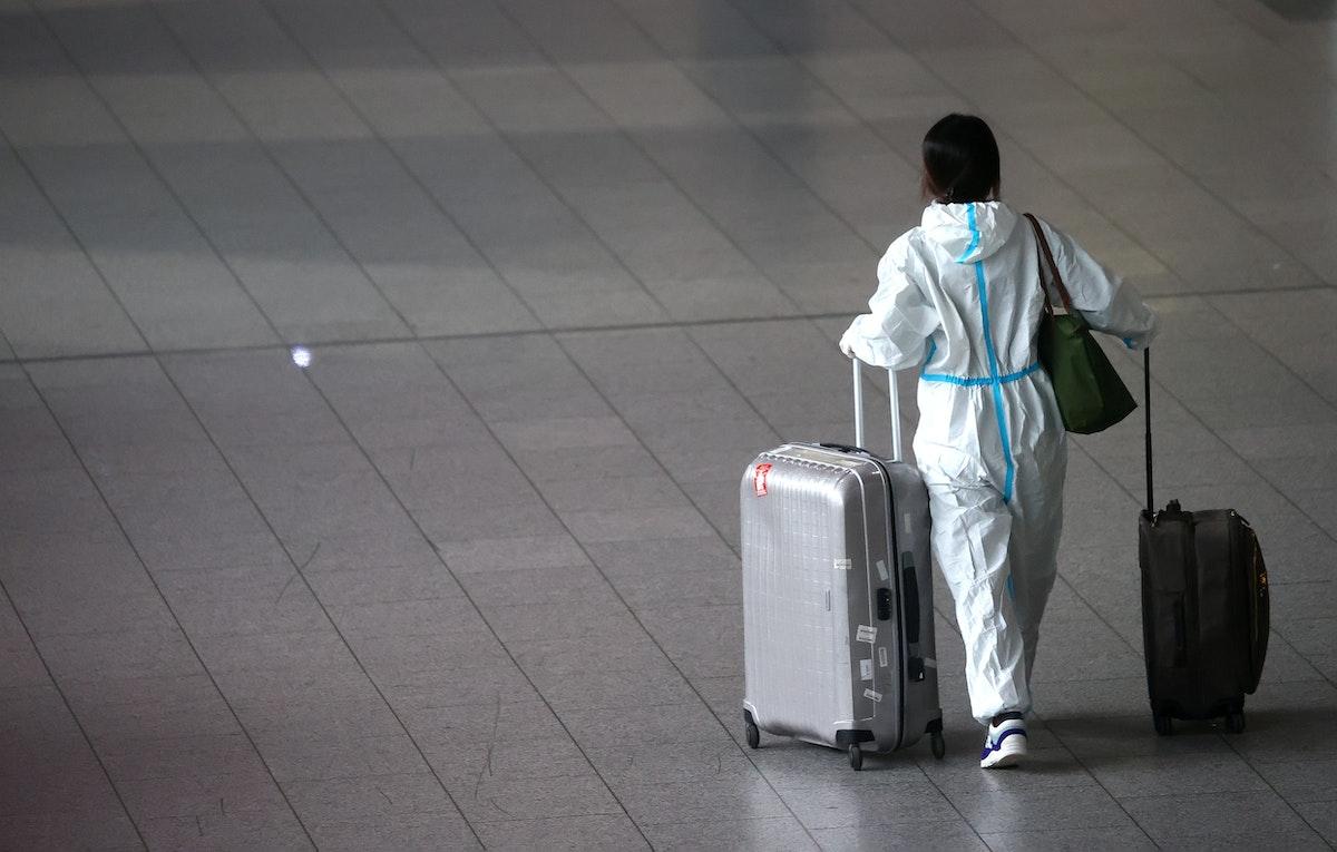 مسافرة ترتدي بدلة معدات الحماية الشخصية (PPE) أثناء سيرها في صالة مطار فرانكفورت الدولي بألمانيا. 4 مايو 2021 - REUTERS