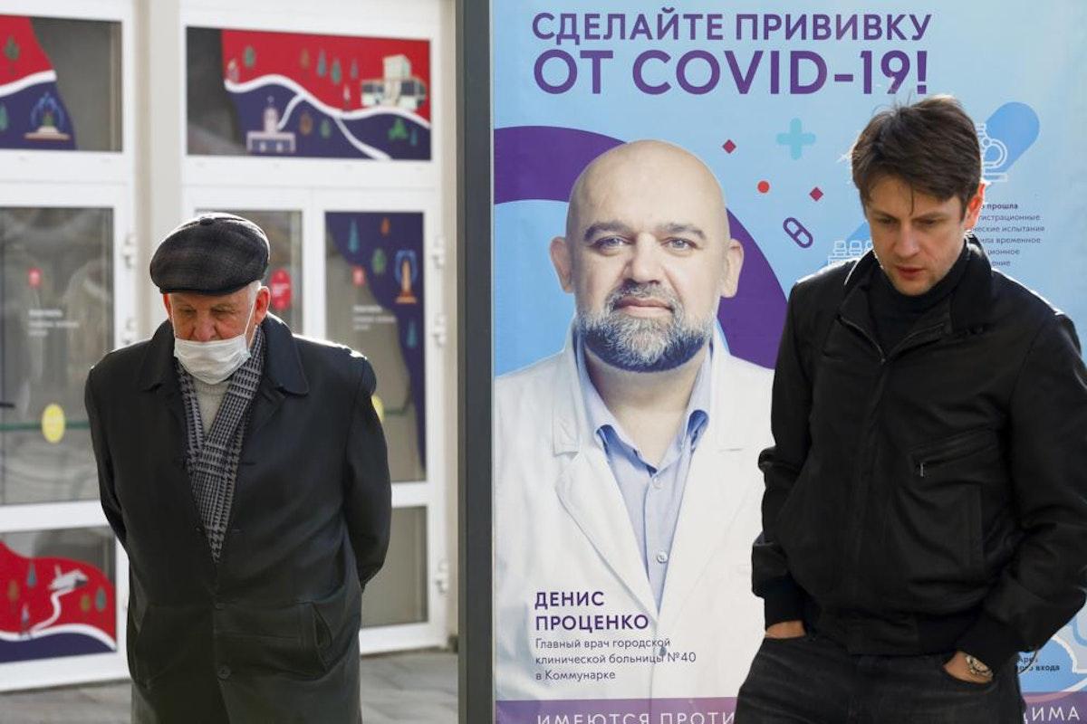 يقفان في موسكو قرب ملصق لطبيب روسي يشجّع مواطنيه على تلقي لقاح مضاد لفيروس كورونا، 2 أبريل 2021 - AP